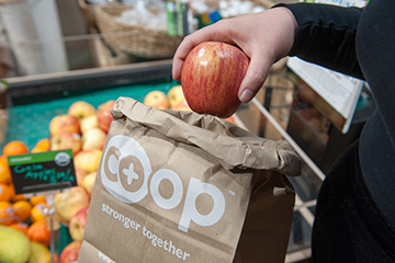 Co-op Partners Warehouse putting apple in bag