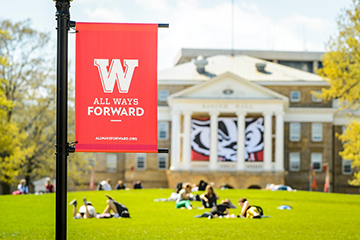 "With an iconic W banner depicting the slogan ""All Ways Forward"" in the foreground, students enjoy the a spring day on Bascom Hill at the University of Wisconsin-Madison on May 4, 2017. (Photo by Bryce Richter / UW-Madison)"