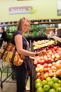 woman picking apples in grocery cooperative