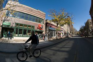 A bicyclist passes by as sunlight shines on the UW Credit Union and other storefronts along the State Street pedestrian mall, just east of the University of Wisconsin-Madison campus in downtown Madison, Wis., during a mild autumn day