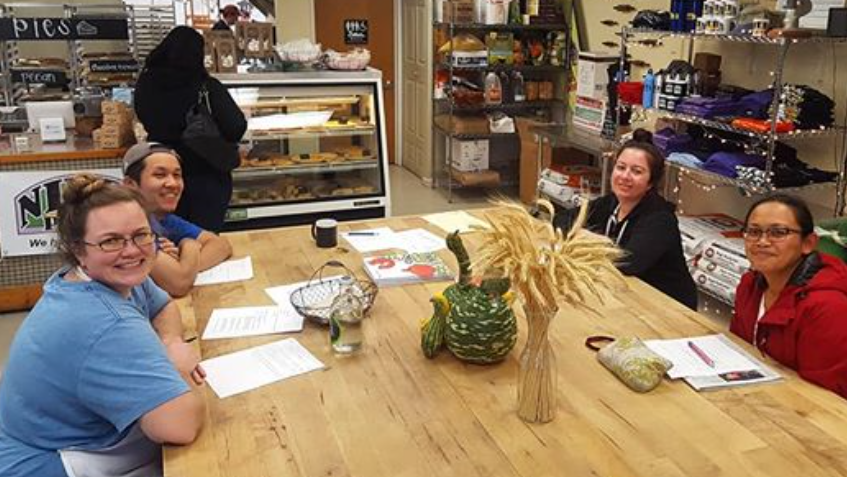 Member for Niles Pie Cooperative sit around a wood table in the pie shop having a meeting.